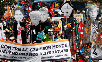 Снимка на деня: Посрещни лидерите от Г-7 с…протест